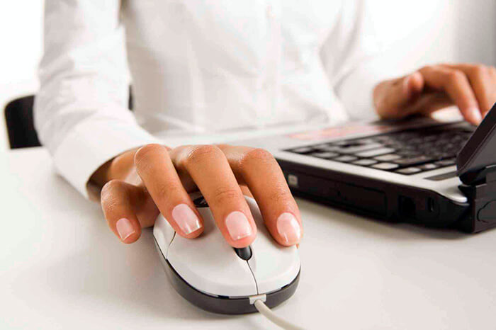 Womanís hands touching computer mouse and keys of black opened laptop